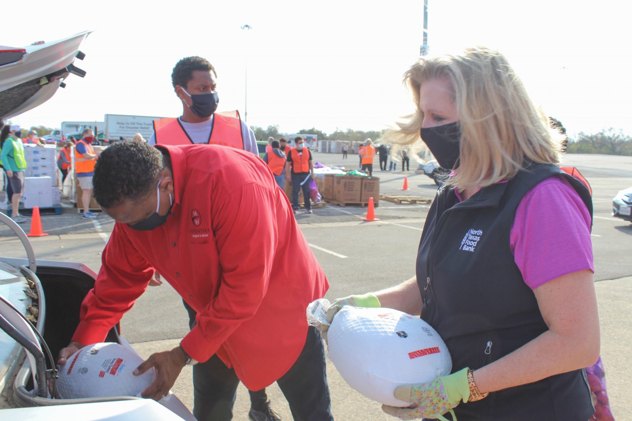 North Texas Food Bank President and CEO Trisha Cunningham helps load turkeys alongside Mitchell Ward with MWL Cares at The Big Give mobile distribution at Fair Park on Nov. 14, 2020. | Photo by Liana Solis