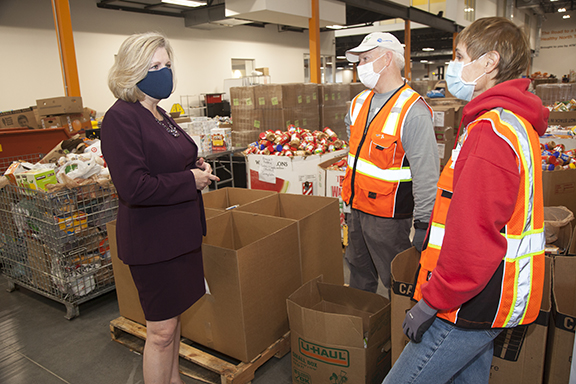 Trisha Cunningham, CEO of North Texas Food Bank speaking with volunteers Jill Mendenhall and Max Chesser