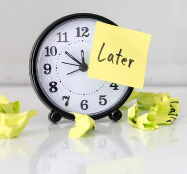 Later Post It on Clock Indicating Procrastinating
