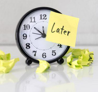 Later Post It on Clock Indicating Procrastinating